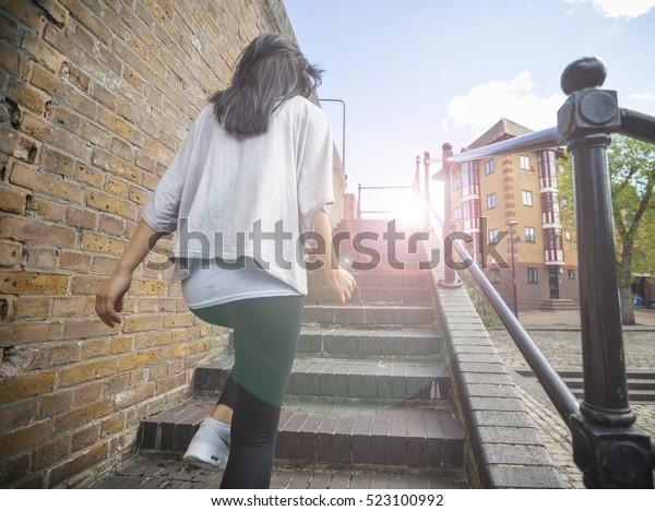Hintere Ansicht der jungen Frau, die die Treppe hinaufgeht