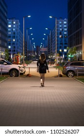 Rear view of young woman wearing black coat walking down the street, street lights towards her. A female with beautiful legs and long hair goes along the night city sidewalk.