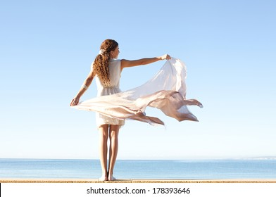 Rear view of a young woman wearing a silk dress and rising a floating sarong up with her arms against a bright blue sky and sea on a holiday beach, outdoors. Travel and healthy lifestyle.