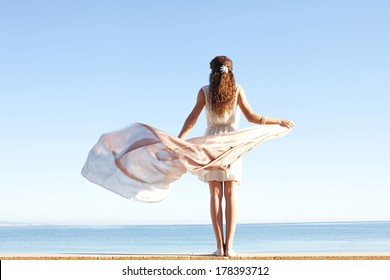 Rear view of a young woman wearing a silk dress and holding a floating sarong with her hands against a bright blue sky and sea on a holiday beach, outdoors. Travel and healthy lifestyle.