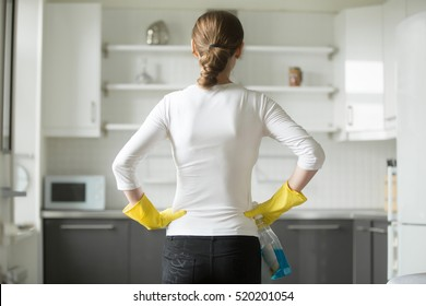 Rear view of young woman wearing rubber protective yellow gloves, holding rag and spray bottle detergent, hands at her hips, observing clean and sparkling kitchen. Home, housekeeping concept