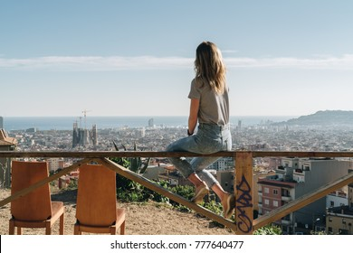 Rear view of young woman wearing in stripped t-shirt sitting on high point and looking at cityscape, next to two empty chairs. Summer sunny day, rear view, bird's eye view of city, cityscape, horizon.