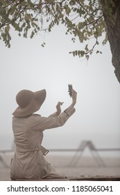 Rear view of young woman woman wwearing hat and coat in autumn scenery lonely autumn beach using smartphone