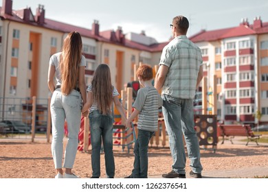 rear view.a young family is looking at a new apartment building