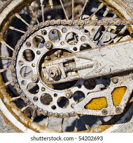 The rear wheel of a motorcycle with a chain, covered with dirt