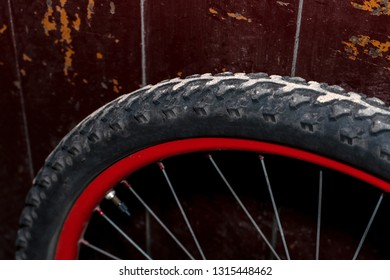 The rear wheel of a mountain bike stands against the background of an old wooden door. Red rim. Tire close up. Bicycle repair. Modern workshop.