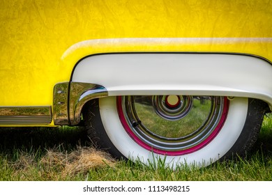 The rear wheel skirt and white wall tires of a fifties American classic car.