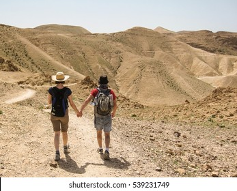 The rear of a young couple holding hands and walking on a trail on their hiking and camping travel. with desert mountains on the background.
