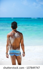 Rear of a young man standing on the beach and facing the Caribbean