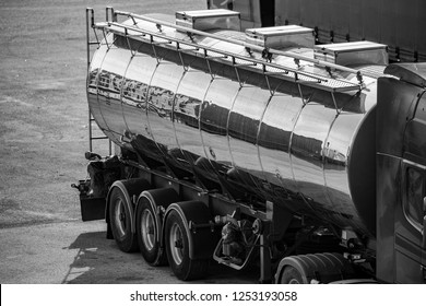 The rear-side part of shiny tin fuel truck, black and white side high-angle view reflecting containers in an open area