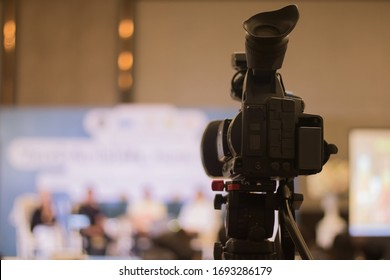 Rearview of black television camera While recording a news video Resting on a tripod With a bokeh background, people talking In the hotel hall The room has a warm glow of orange colour tones.