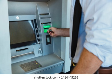 A rear-view close-up shot of an unrecognizable businessman using an ATM machine in Perth Australia, he is inserting his credit card to withdraw money.