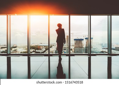 Rearview of a female entrepreneur on the top of a modern business office skyscraper standing near big panoramic windows and pensively looking at a construction site and the cityscape; reflecting floor