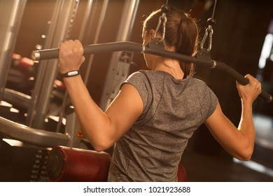 Rearview horizontal shot of a sportswoman exercsiing at the gym doing wide-grip lat pulldown machine muscles flexing strengthening powerful healthcare activity athletics physique concept