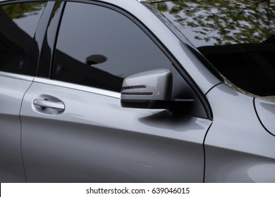 Rear-view mirror closed for safety at car park,  Rear-view mirror of gray car , black tinted glass