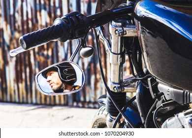 Rear-view mirror reflection of a modern biker sat on classic motorcycle. Outdoor portrait and urban lifestyle