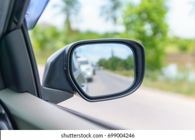 Rearview mirror with traffic jam on the asphalt rural road at countryside. travel or traffic of transportation concept