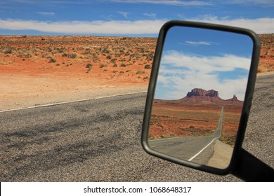 Rearview Mirror view of the road running through Monument Valley, Utah, USA