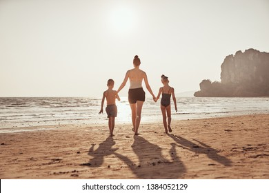 Rearview of a Mother and her two little children walking hand in hand along a sandy beach during summer vacation