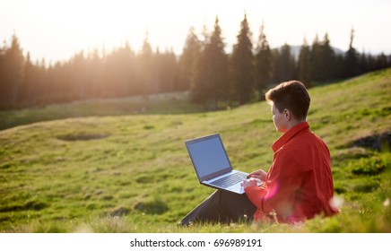 Rearview shot of a female relaxing on the grass using her laptop copyspace sunlight morning blissful nature outdoors travelling tourism freedom technology online internet connection
