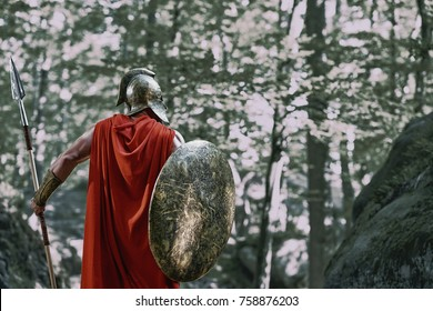 Rearview shot of a Roman soldier walking through the woods with a shield in his hand copyspace.