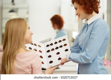 Rearview shot of a young beautiful woman choosing hair dye color from the chart talking to her hairdresser at the beauty salon profession occupation helpful friendly advice job service hair care.