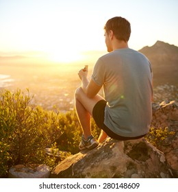 Rearview shot of a young guy on a nature trail pausing to eat a protein bar while watching the sunrise
