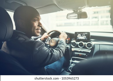 Rearview of a smiling African businessman driving his car during his morning commute to work through the city