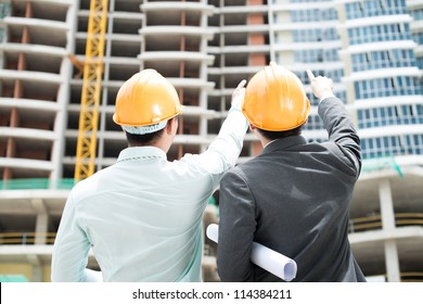 Rear-view of two foremen pointing at the newly-built storey