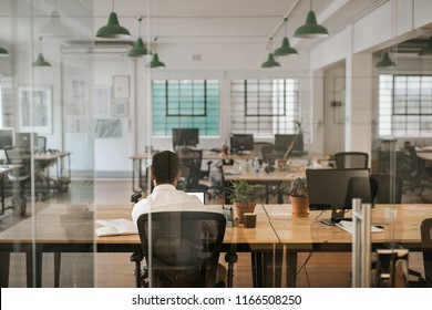 Rearview of a young businessman sitting alone at his desk in an office working on a laptop and going over paperwork