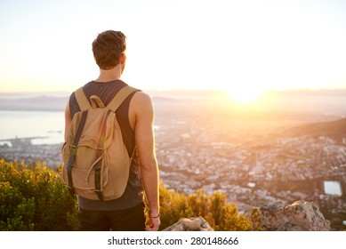 Rearview of a young man with a backpack watching the sunrise from a nature trail above the city
