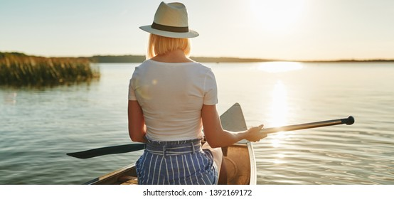 Rearview of a young woman enjoying the view while paddling a canoe on a still lake on a late summer afternoon