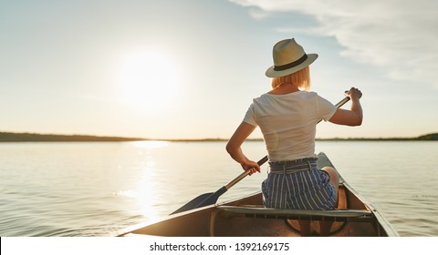 Rearview of a young woman looking at the scenery while paddling a canoe on a scenic lake on a late afternoon in summer