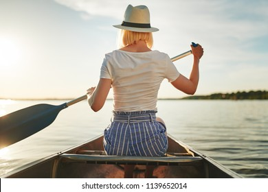 Rearview of a young woman looking at the view while paddling a canoe on a still lake on a late summer afternoon