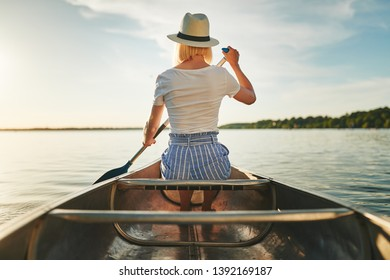 Rearview of a young woman looking at the view while paddling a canoe on a tranquil lake on a sunny afternoon in summer