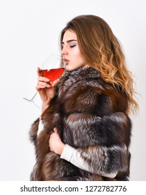 Reasons drink red wine in wintertime. Woman drink wine. Girl fashion makeup wear fur coat hold glass alcohol. Elite leisure. Lady fashion model curly hairstyle enjoy elite wine. Wine culture concept.