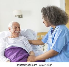 Reassuring confident african female doctor visiting elderly caucasian patient in hospital bed.