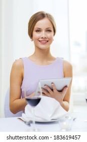 reastaurant, technology and happiness concept - smiling young woman with tablet pc computer and glass of red wine at restaurant