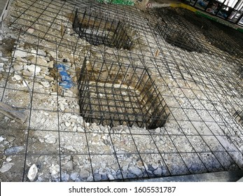 Rebar steel for concrete foundation and reinforcing steel for concrete flooring after packing the ground of an existing building to replace damaged floor with new concrete one with foremen supervision