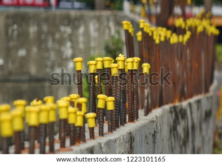 Rebar steel rods with yellow end protection caps, image features selective focus