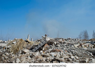 The rebar sticking up from piles of brick rubble, stone and concrete rubble. Remains of the destroyed industrial building. In the background, you can see the remnants of smoke clubs.