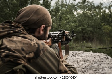 Rebel aiming an assault rifle at target, hidden behind concrete obstacle - rear view