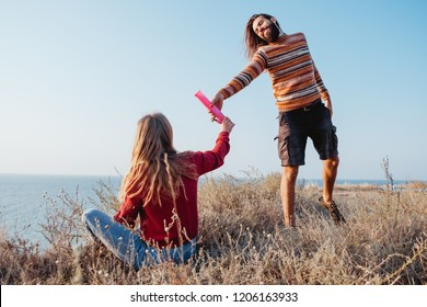 Rebel hipster woman and man friends passing each other a pink water bong outdoors.