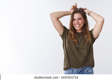 Rebellious charming woman showing inner devil having fun stubborn, smiling broadly playing holding index fingers behind head imitating horns, squinting happily, laughing out loud white background