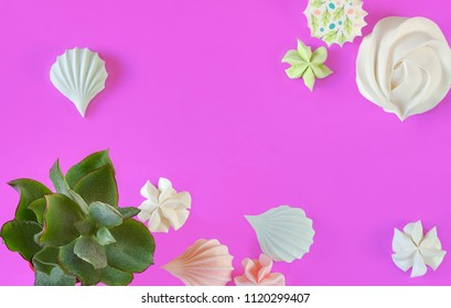 Rebellious color schemes of the flat lay minimal summer white, blue and pink organic candy meringue dessert and succulents on punchy ultra violet pastel background with a copy space