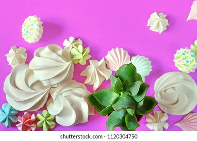 Rebellious color schemes of the flat lay minimal summer white, blue and pink organic candy meringue dessert and succulents on punchy ultra violet pastel background with copy space