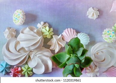 Rebellious color schemes of the flat lay minimal summer white, blue and pink organic candy meringue dessert and succulents on punchy blue food pastel background with a copy space