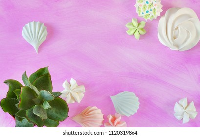 Rebellious color schemes of the flat lay minimal summer white, blue and pink meringue dessert and succulents on punchy ultra violet pastel background with a copy space