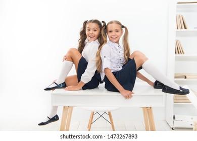Rebellious spirit. School club. Little schoolgirls classmates friendly kids. Schoolgirls friends sit on desk. Best friends relaxing. Schoolgirls tidy hairstyle relaxing having rest. School uniform.