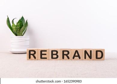 REBRAND word written on wood block on a light background
